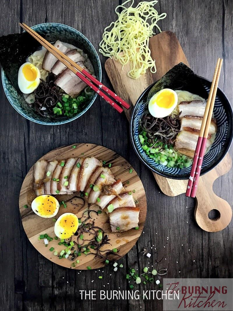 Tonkotsu Ramen with Pork Belly Chashu in big blue bowls, with cha shu at the side on a brown wooden board