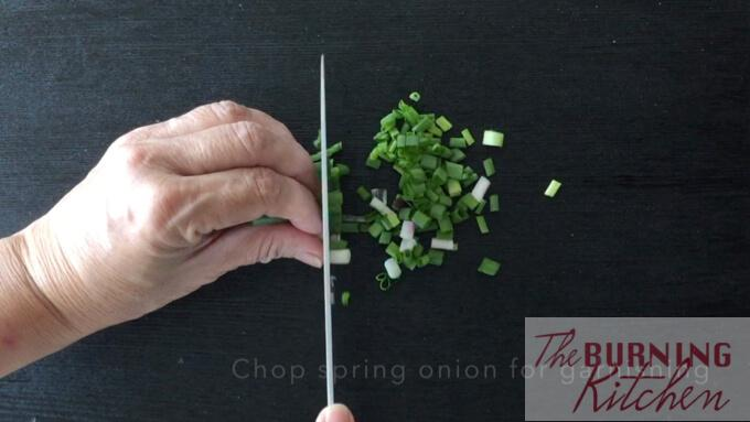 chopping spring onions on black chopping board