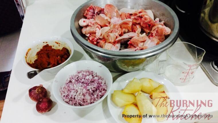 Chicken pieces, shallots, potatoes and curry paste in individual bowls and pots