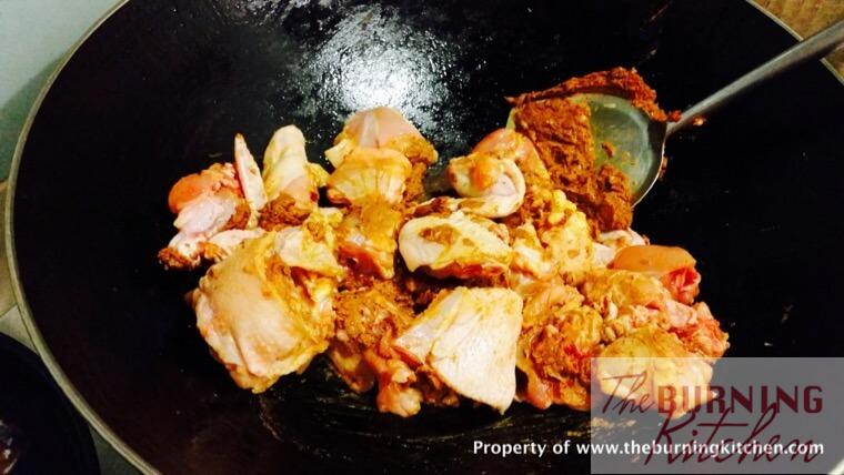 Frying chicken pieces in curry paste in wok