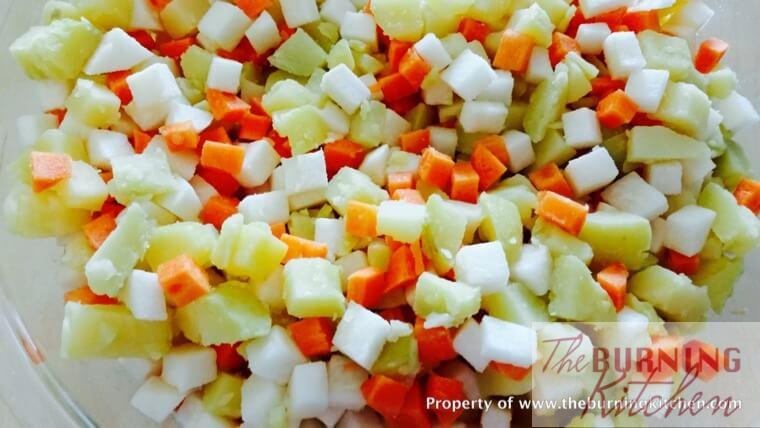 Diced carrots, potatoes and turnips on white bowl
