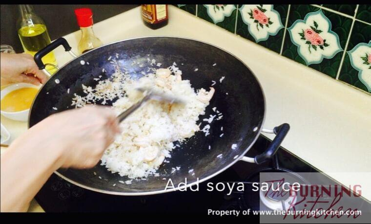 Adding fried rice to sautéed prawns in wok