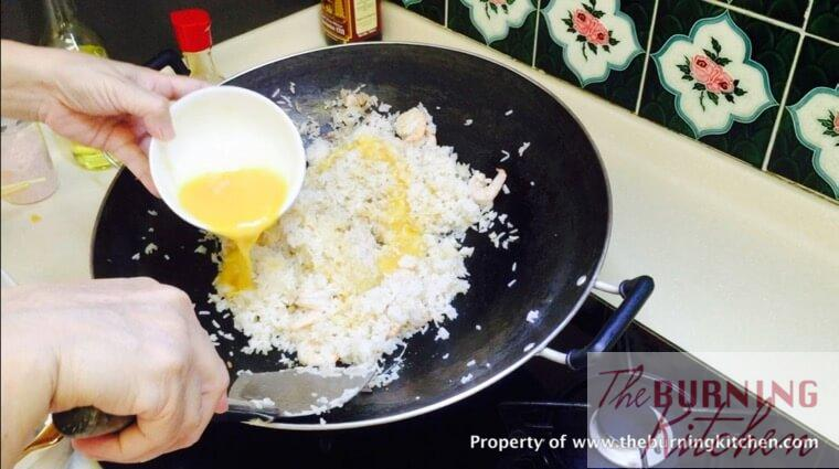 Pouring beaten eggs into fried rice mixture
