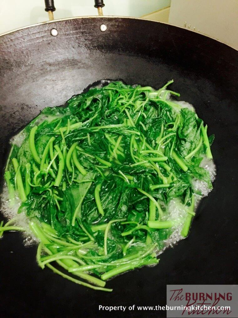 spinach being cooked in ikan bilis broth in wok