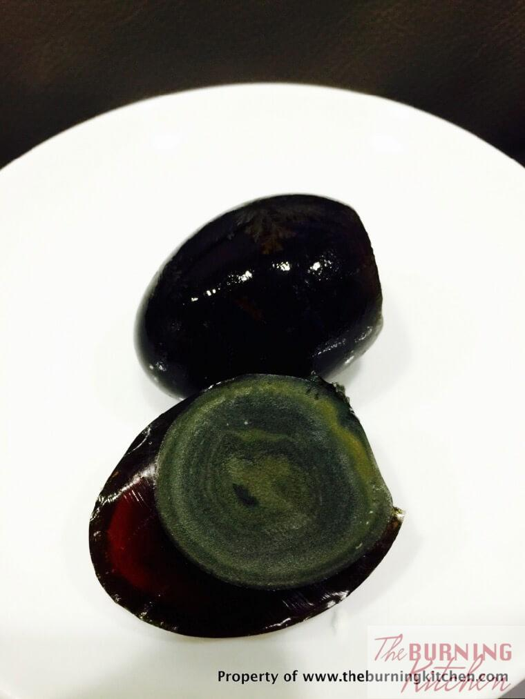 Century egg unshelled on white plate.