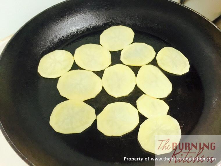 Pan frying potato slices in wok