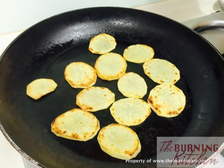 Pan frying potato slices in wok