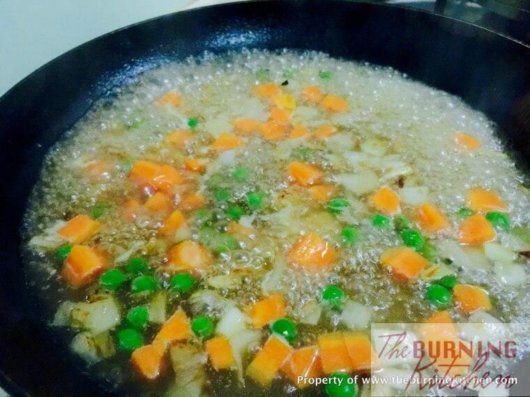 Stir-frying diced carrots, onions and peas and sauce in pan