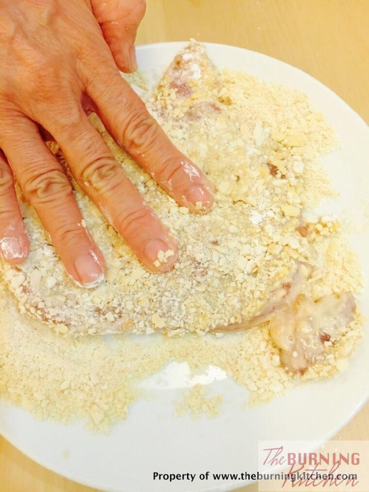 Coating pork chop in cornflour and egg mixture in biscuit crumbs on white plate