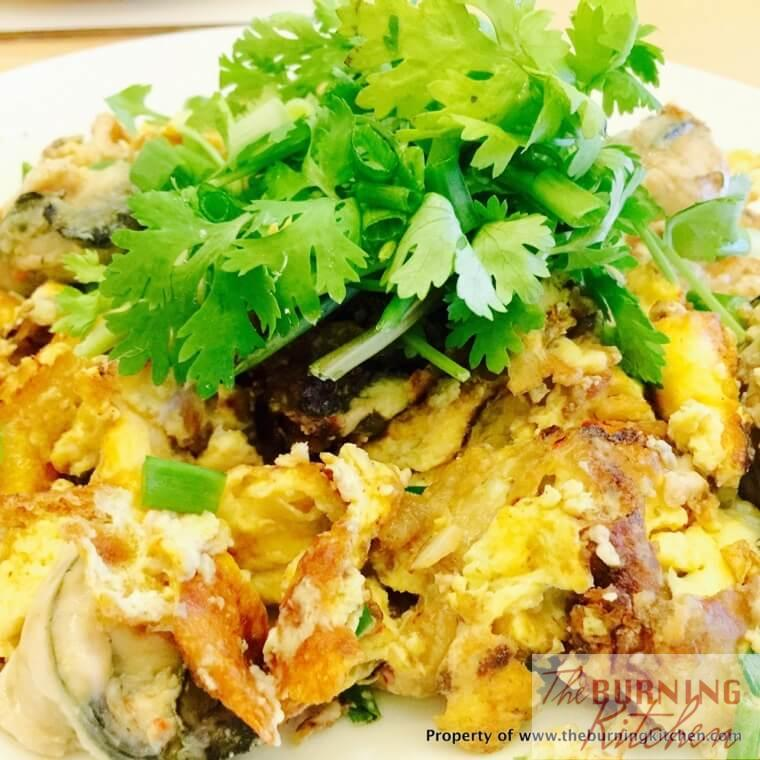 fried oyster omelette on white plate with parsley garnishing