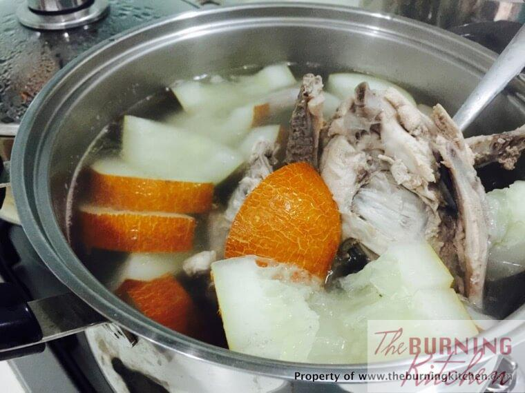 old cucumber, chicken bones, in a metal pot with boiling water