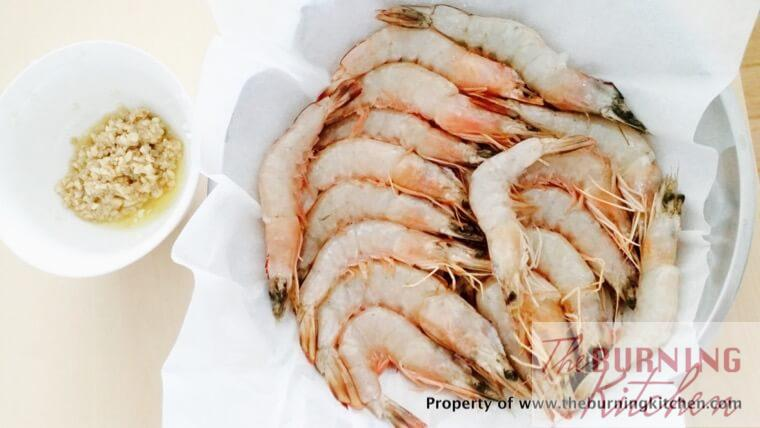 prawns arranged neatly on baking paper in circular metal tray, with garlic at the side