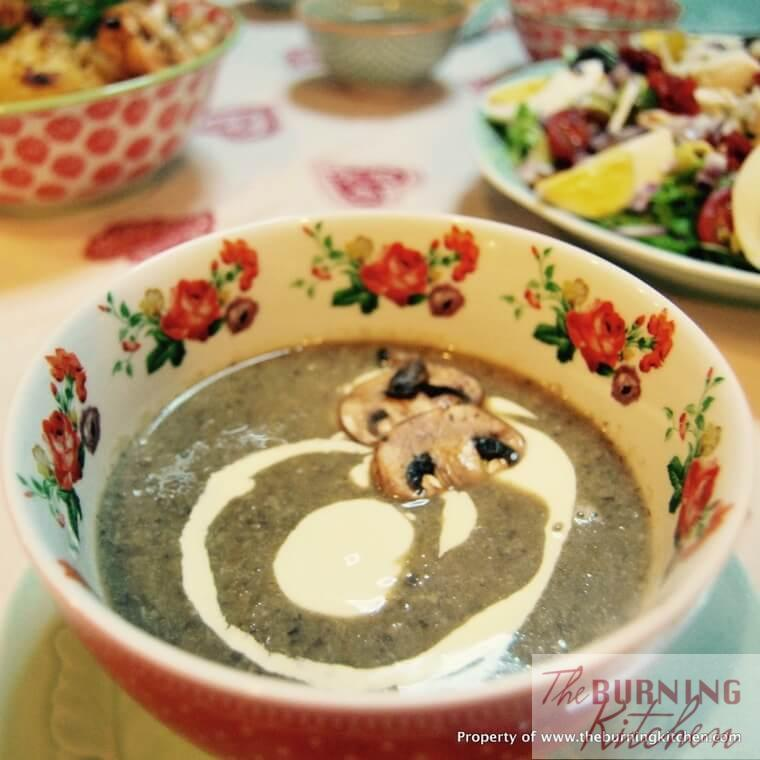Bowl of mushroom soup with cream and mushroom on top