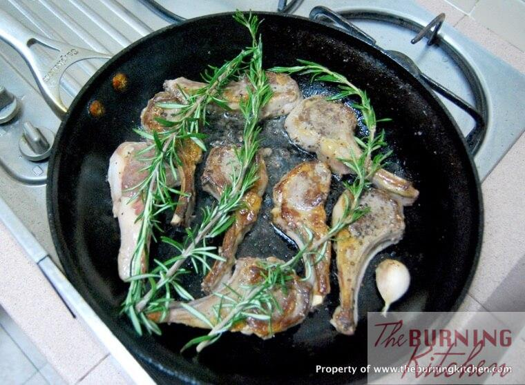 Pan frying lamb cutlets with rosemary sprigs in pan
