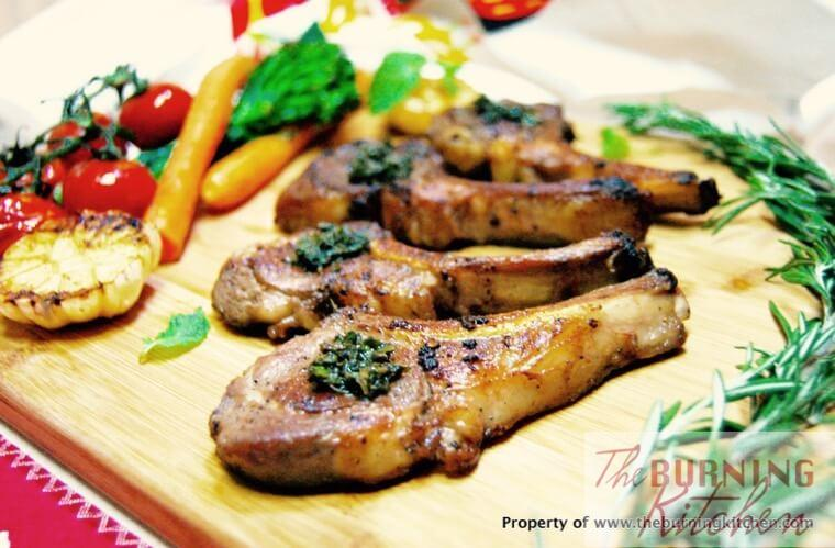 Rosemary lamb cutlets on a wooden chopping board with rosemary sprigs and roasted vegetables