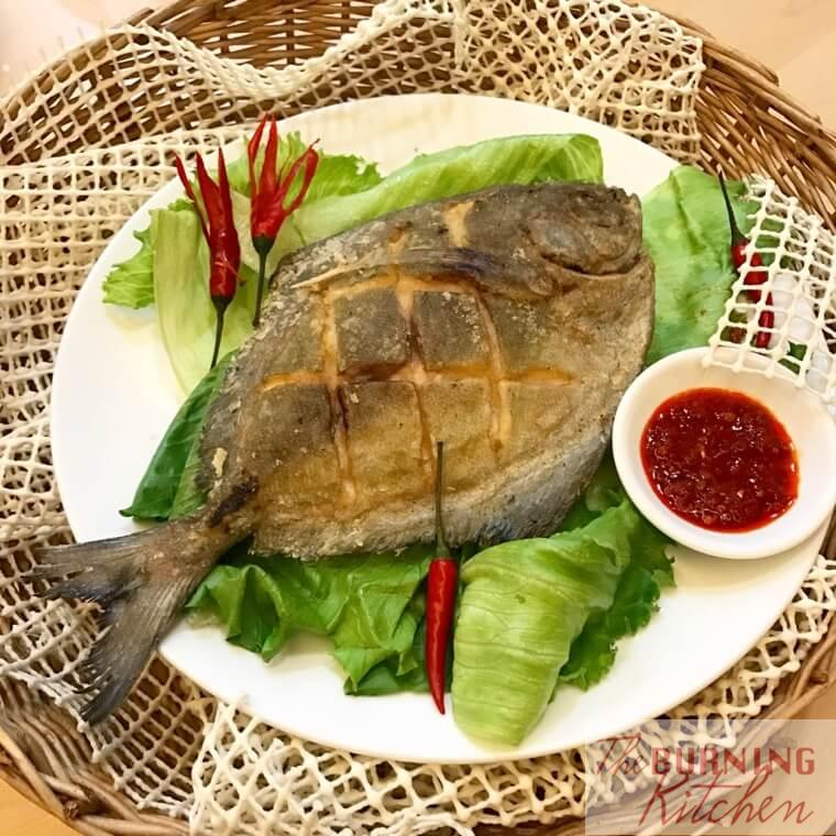 Ultra Crispy Fried Pomfret on lettuce on white plate with chilli sauce at the side