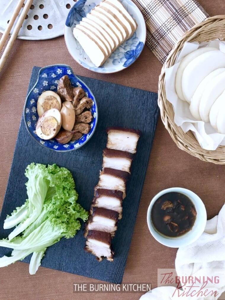 Braised Pork belly on black chopping board with lettuce, eggs, tau kwa and buns at the side