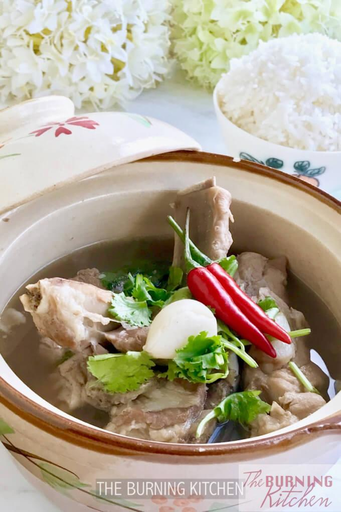 Bak Kut Teh Soup with pork ribs, chilli, garlic and garnishing in claypot, with bowl of white rice in background