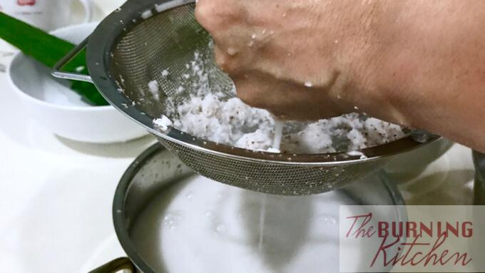 squeezing coconut gratings through a sieve into a pot