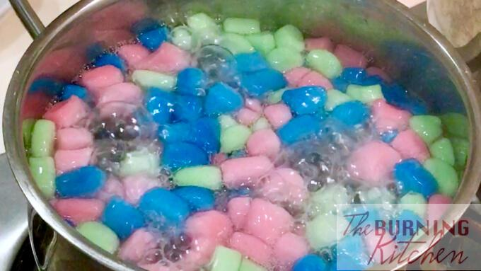 boiling red, blue and green tapioca cubes in boiling water in pot