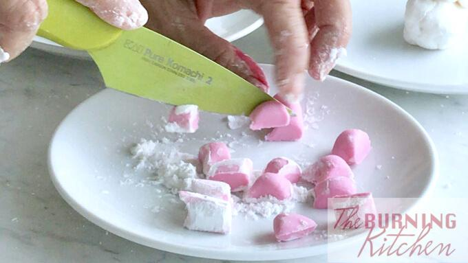 cutting red tapioca flour into small cubes on a white plate