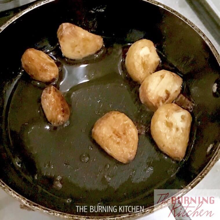Stir frying whole garlic in pan