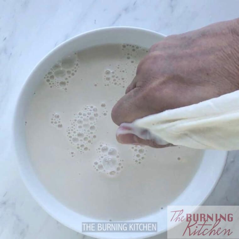 Squeezing soy milk out of muslin cloth with hand