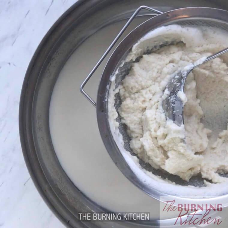 Sieving blended soy beans through strainer with spoon