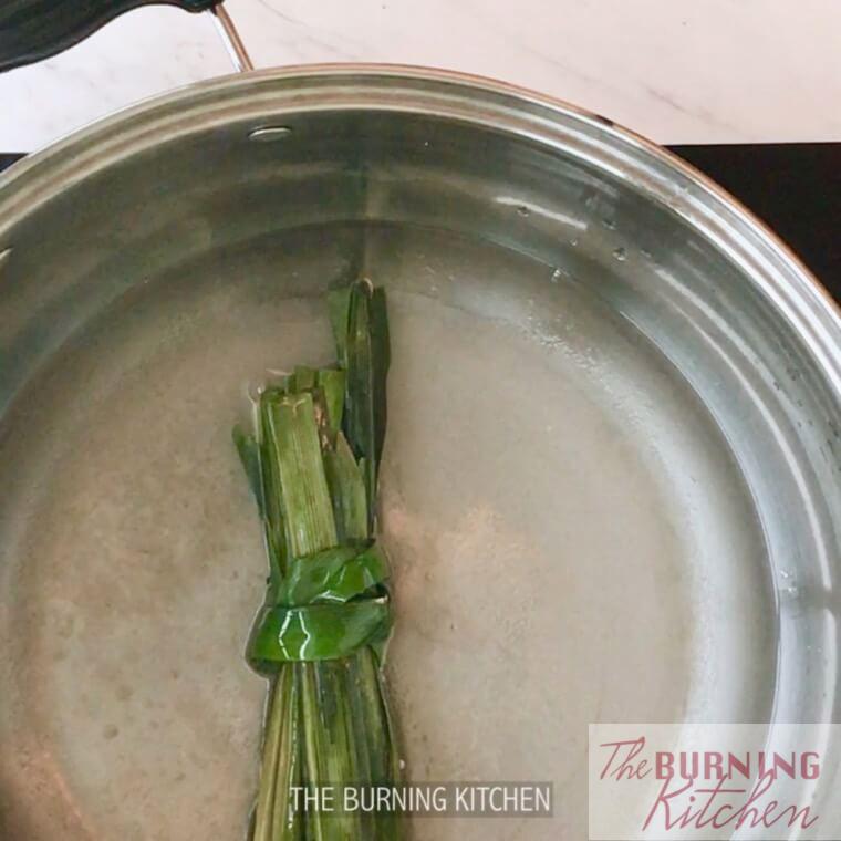 Boiling pandan leaves in sugar water in metal pot