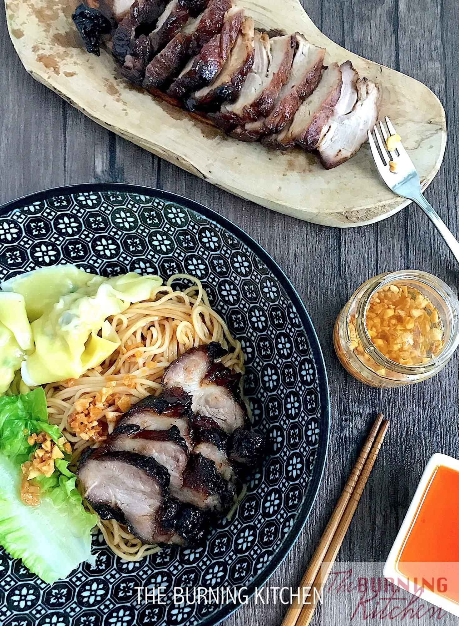 Charsiew with noodles on plate and chopping board