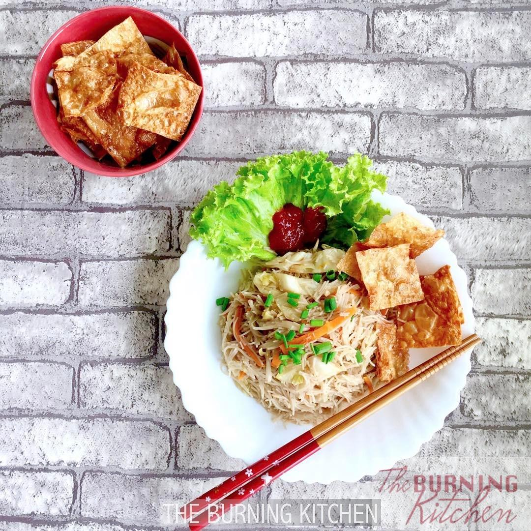 Vegetarian bee hoon on white plate with chopsticks and bowl of fried mock goose on the side