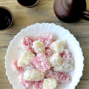 steamed tapioca cake coated in grated coconut on white plate with accompanying chinese tea cup and pot