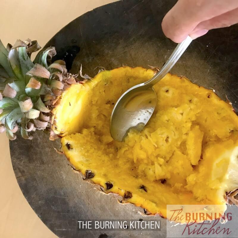 Scooping out pineapple flesh out of pineapple