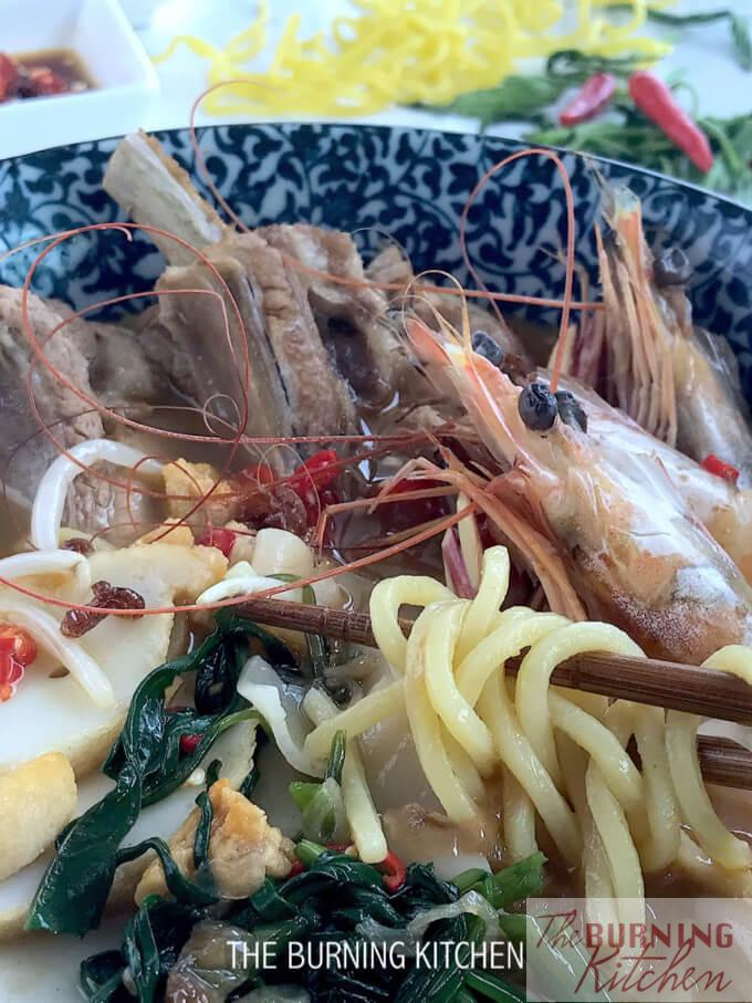Prawn Noodles With Pork Ribs in blue bowl close up