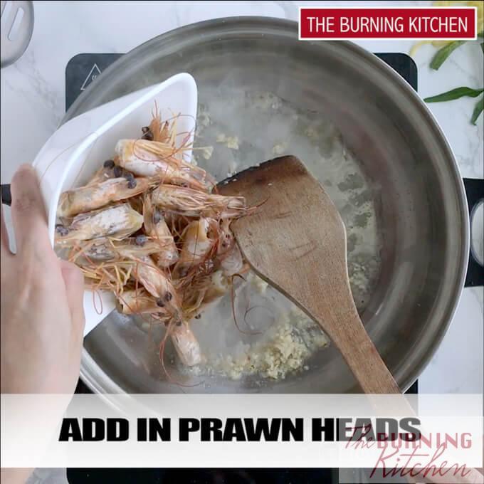 Frying prawn heads with garlic in metal pan