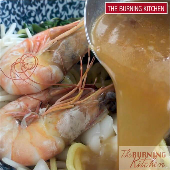 Pouring broth into prawn noodles