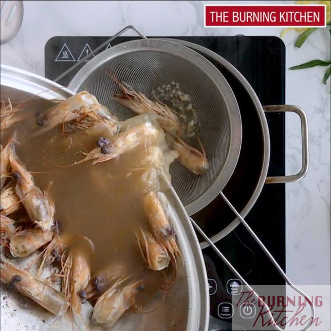 Straining prawn broth with prawn heads with strainer into metal pot