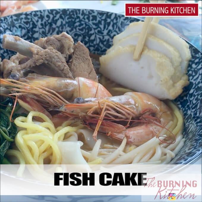 Adding fish cake to prawn noodles