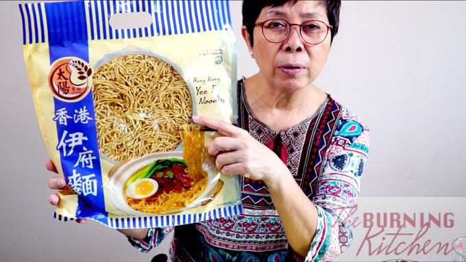 The Burning Chef holding up a big packet of Yee Fu noodles