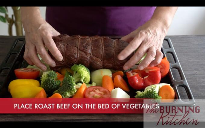 Placing roast beef in the middle of vegetables