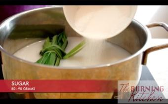 Adding sugar into a pot of coconut milk and pandan