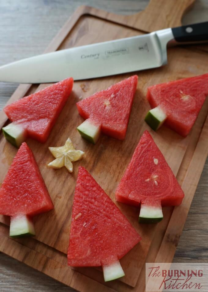 Watermelon Christmas Trees on a wooden chopping board with knife in the background