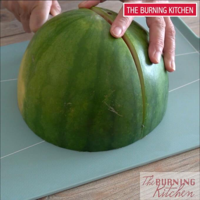 Cutting half a watermelon into quarters