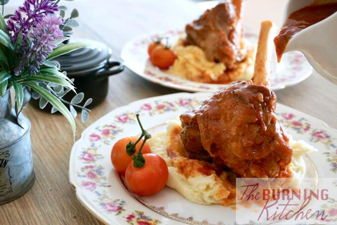 Braised Rosemary Lamb Shank on mashed potatoes with rosemary leaf and roma tomatoes