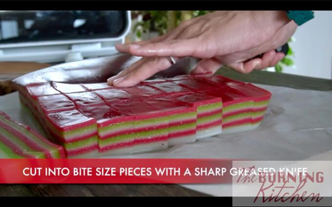 Cutting kueh lapis with a knife into smaller blocks