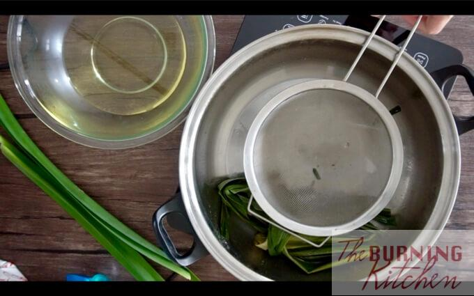Pandan leaves in a metal pot with a sieve over it