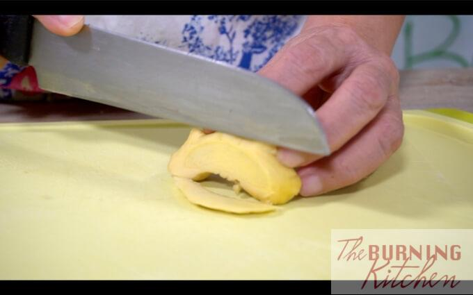 Slicing ginger on chopping board
