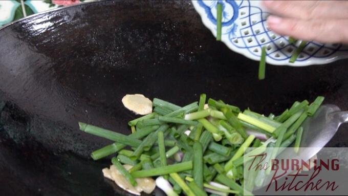 Stir frying sliced ginger and spring onion in wok