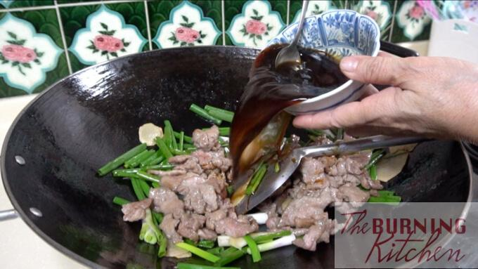 Pouring sauce over stir fried Beef with Ginger and Spring Onions