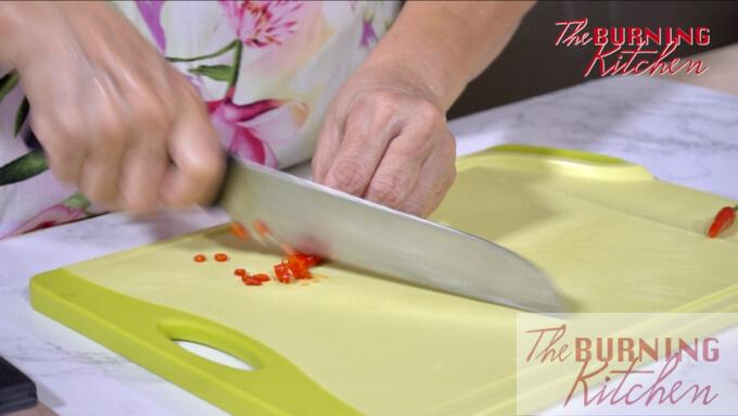 Chopping chilli on a chopping board